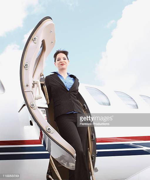 Business woman stepping of corporate jet