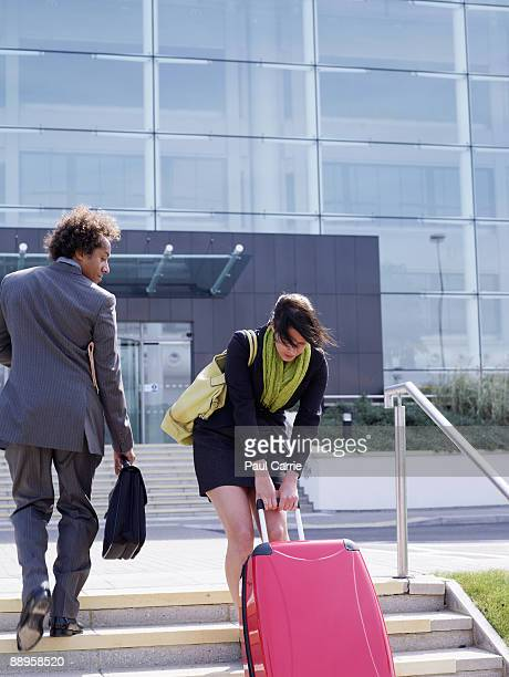 business woman struggling with suitcase up steps m
