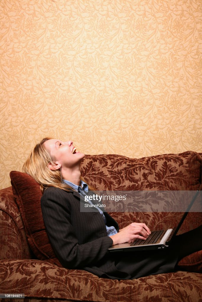 Business woman surfing the net and laughing in Hotel Room : Stock Photo