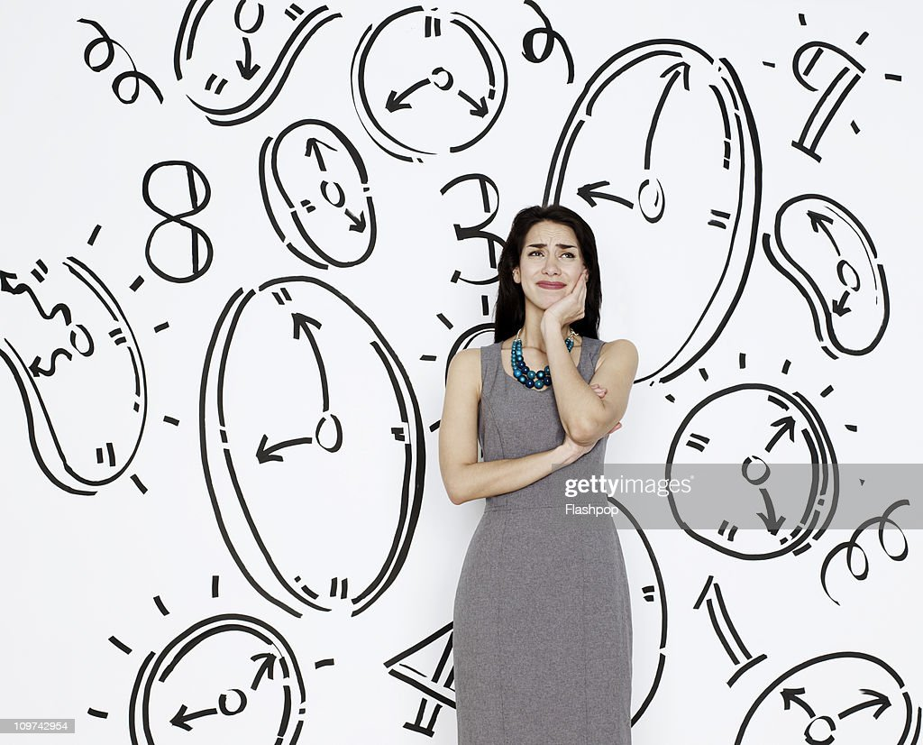 Business woman surrounded by clocks : Stock Photo