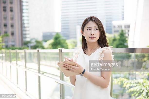 Business woman taking note in city location