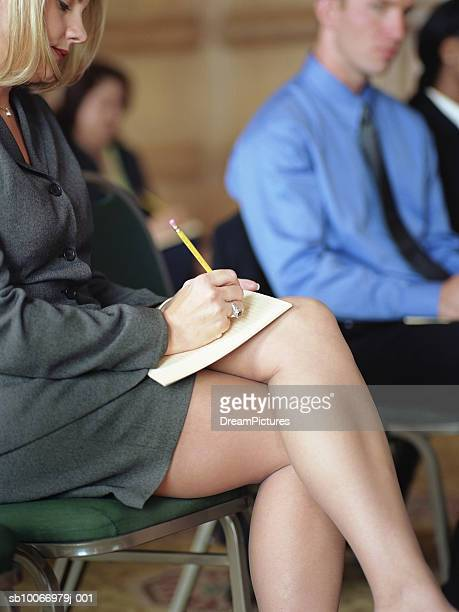 business woman taking notes at conference, side view - legs and short skirt sitting down stock photos and pictures