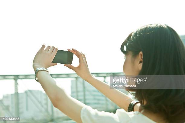 Business woman taking photograph with smartphone