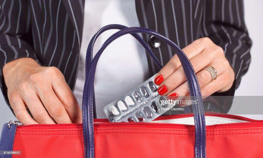 Business Woman Taking Pills From Her Handbag Stock Photo