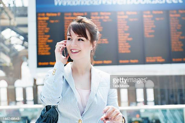 business woman talking on mobile at station