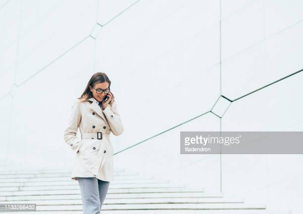 business woman talking on the phone - hands in pockets stock pictures, royalty-free photos & images