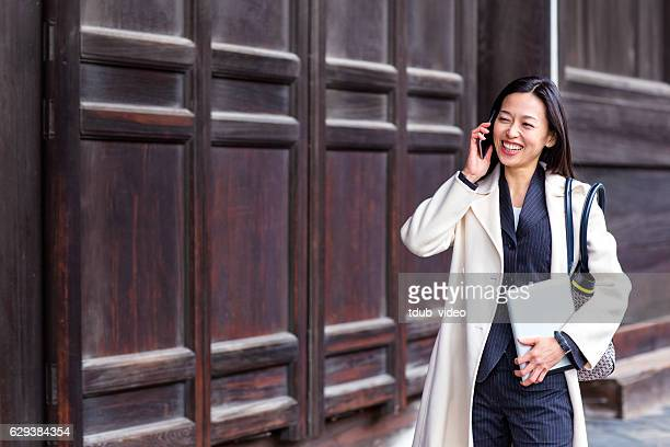 business woman talking on the phone while walking - tdub_video stock pictures, royalty-free photos & images