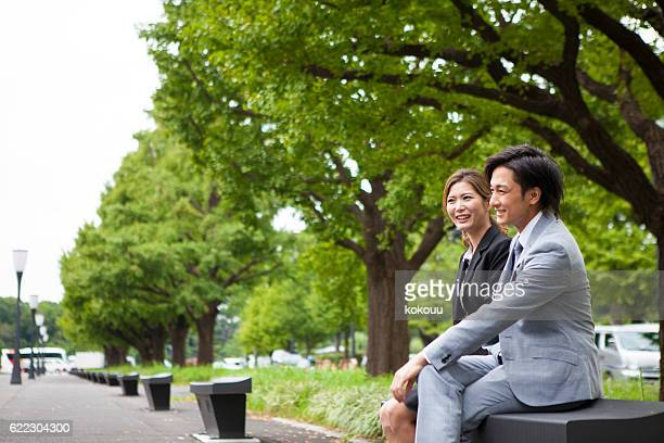 Business woman talking with a partner in the park