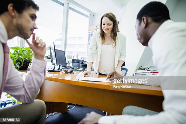 Business woman talking with colleagues in office