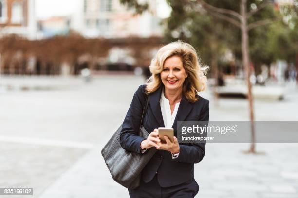 zakelijke vrouw tekstoverseinen op straat - alleen één oudere vrouw stockfoto's en -beelden