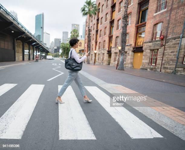 Mensagens de mulher de negócios em seu telefone celular quando atravessava a rua