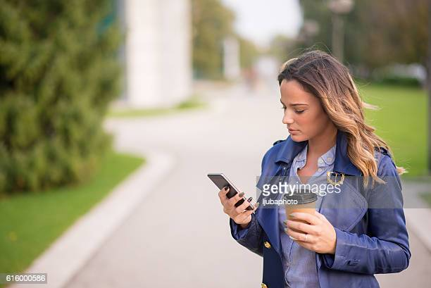 Business woman texting on her phone and holding coffee to