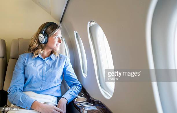 Business woman traveling by plane wearing headphones