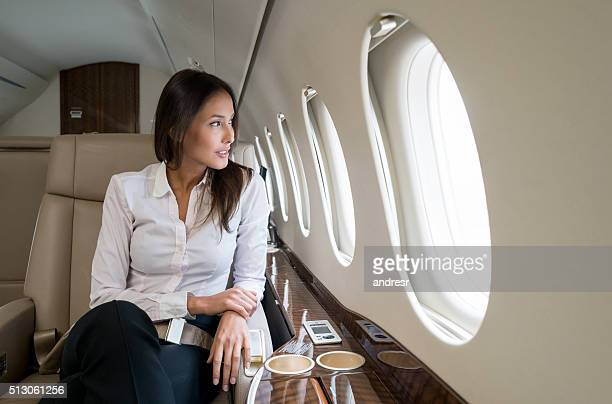 business woman traveling in a private jet - geschäftsreise stock-fotos und bilder