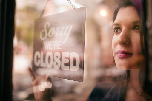 Business Woman Turning Closed Sign on Door of coffee Shop 516317606