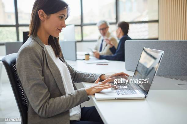 business woman using a laptop in the office. - incidental people stock pictures, royalty-free photos & images