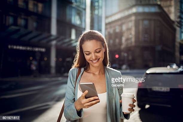 business woman using a phone while walking - unterwegs stock-fotos und bilder