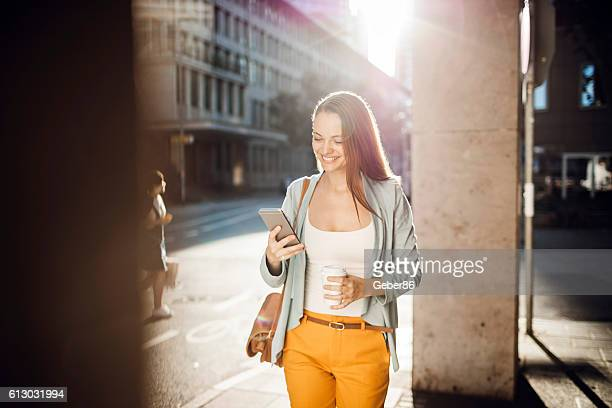 Business woman using a phone while walking