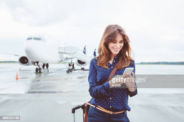 Business woman using a smart phone in front of airplane