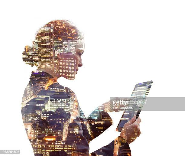 Business woman using a tablet, and city at night.