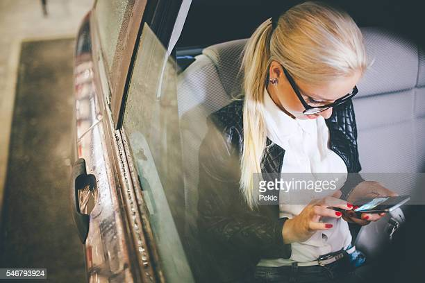 Business woman using cell phone in a taxi
