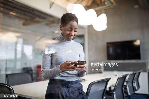 business woman using cellphone in office - pull à col montant photos et images de collection