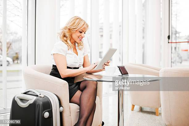 Business woman using digital tablet in hotel lobby.