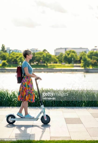 geschäftsfrau mit elektroroller - nur erwachsene stock-fotos und bilder