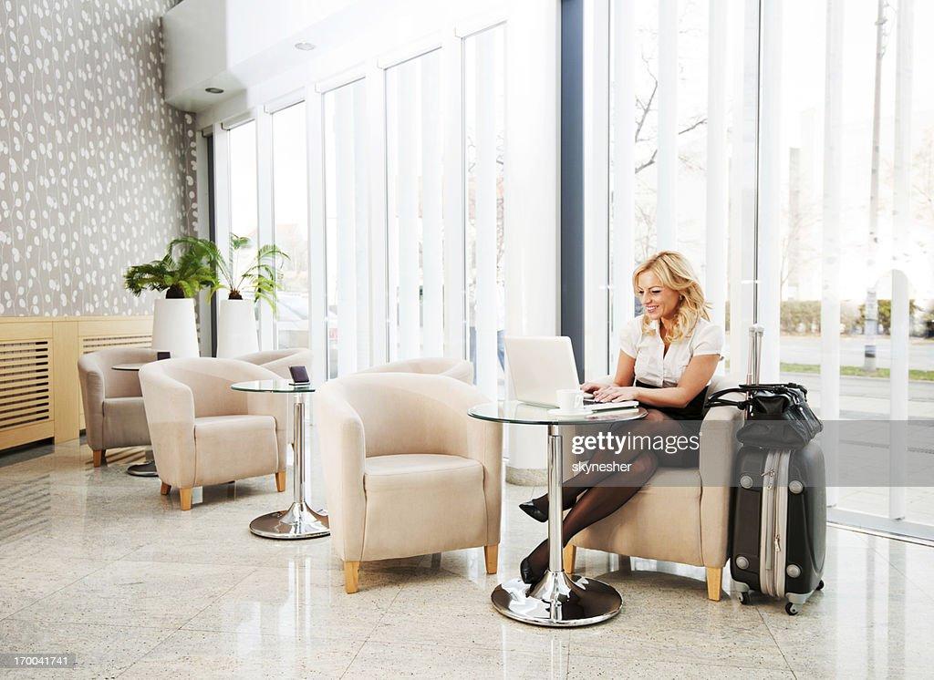 Business woman using her laptop in a hotel lobby. : Bildbanksbilder