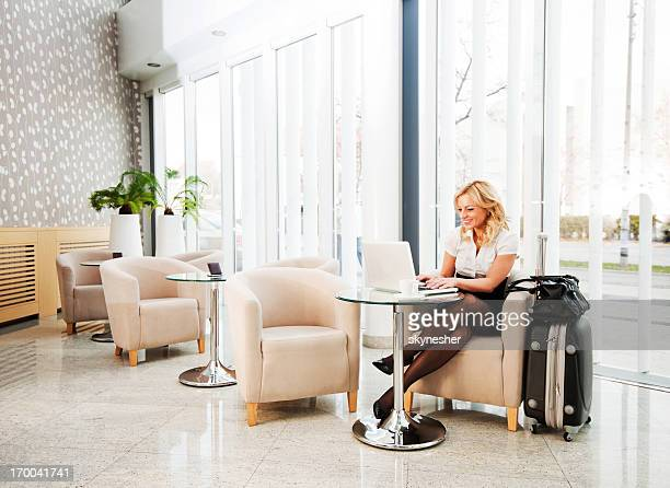 Business woman using her laptop in a hotel lobby.
