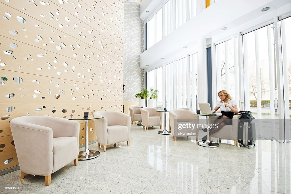 Business woman using her laptop in a hotel lobby. : Stock Photo
