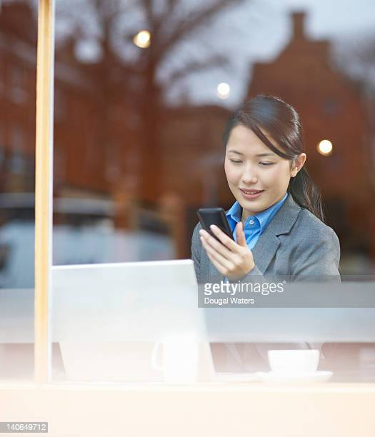 Business woman using laptop and phone in cafe.