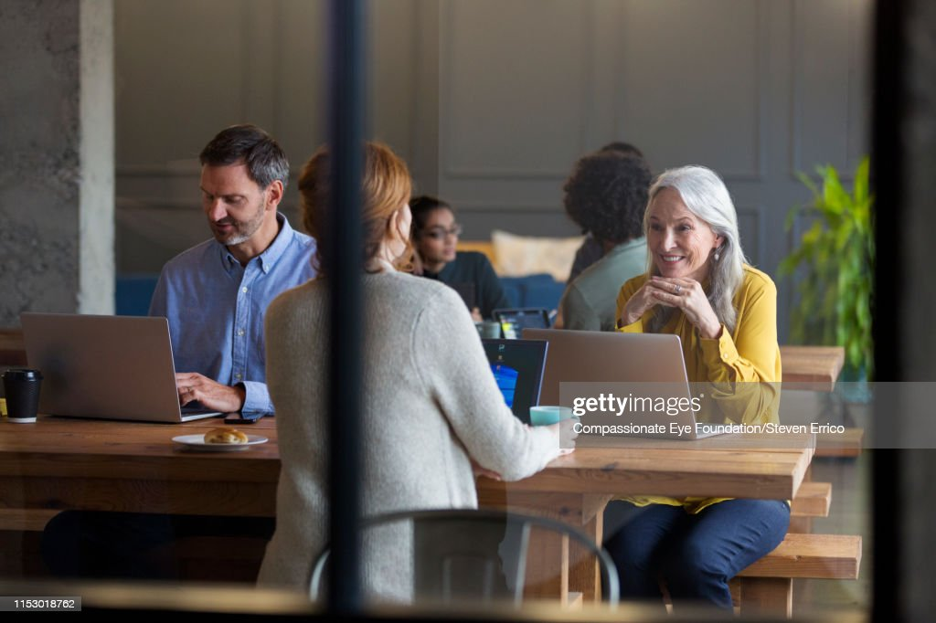 Business woman using laptop in modern open plan office : Stock Photo