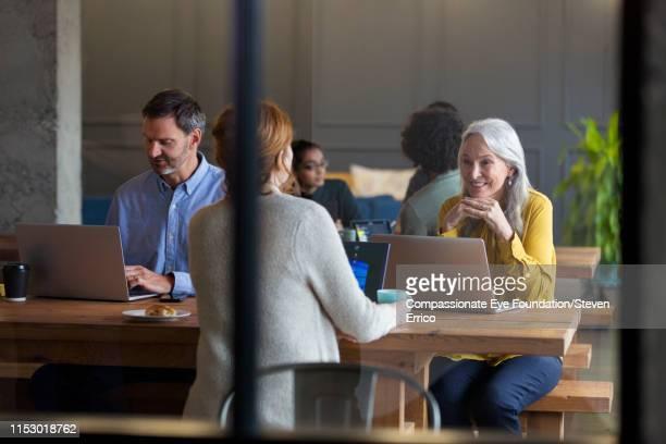 Business woman using laptop in modern open plan office