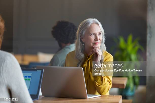 business woman using laptop in modern open plan office - compassionate eye foundation stock pictures, royalty-free photos & images