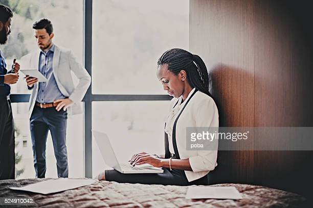 business woman  using laptop on bed in hotel room