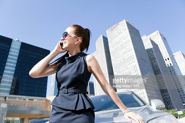 business woman using mobile against a car - sleeveless dress - fotografias e filmes do acervo