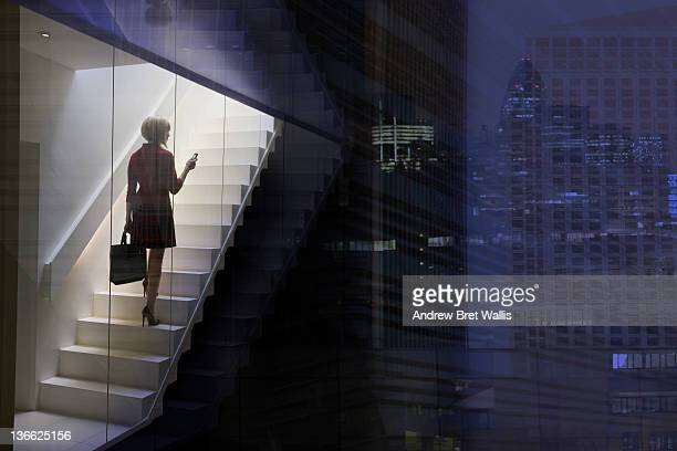 business woman using mobile in the city at dusk - staircase stock pictures, royalty-free photos & images