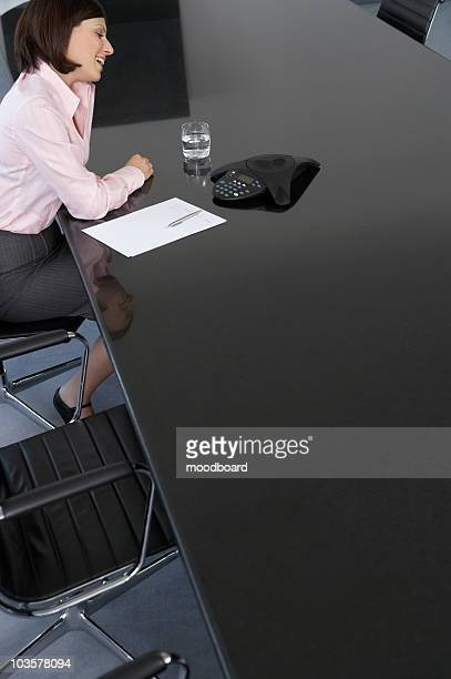 Business woman using mobile phone at conference room table