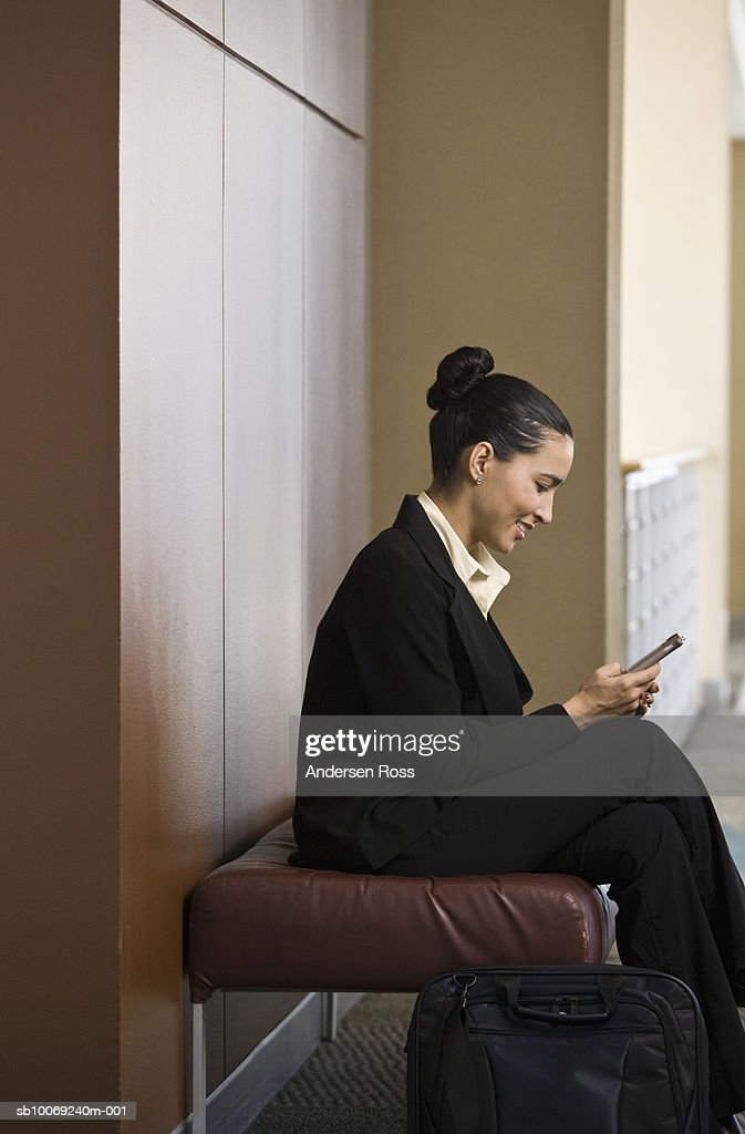 Business woman using PDA, smiling, side view : Stockfoto