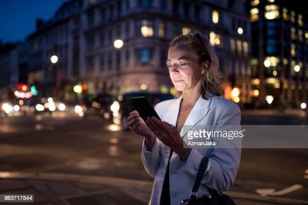 Business woman using smart digital tablet in London