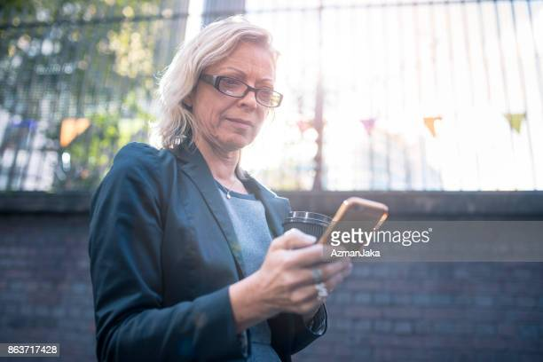 Business woman using smart phone in London