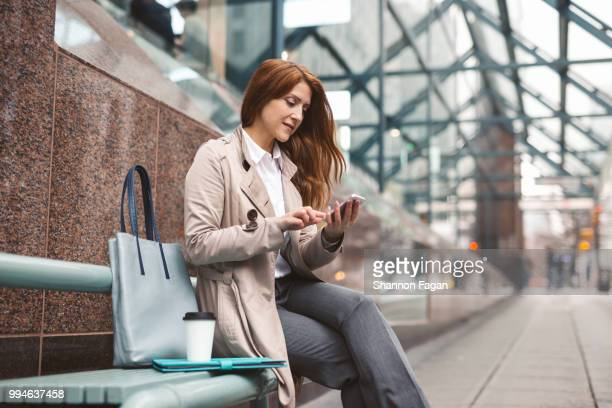 business woman using smart phone on city street - older redhead stock pictures, royalty-free photos & images