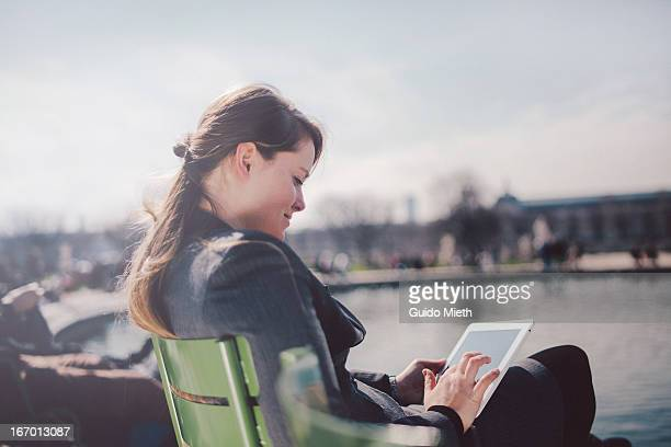 Business woman using tablet pc in park.