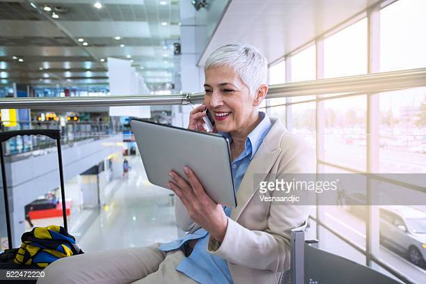 business woman waiting for her flight in airport lounge