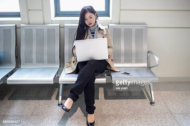 Business woman waiting for train and using laptop