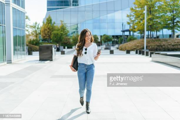 business woman walked while using smartphone. - jeans stock pictures, royalty-free photos & images