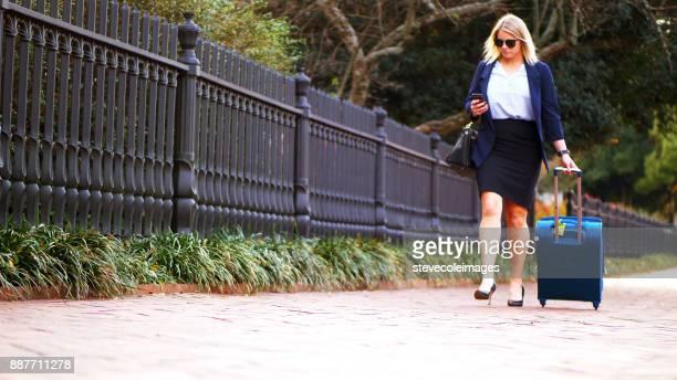 Business woman walking down sidewalk pulling suitcase.