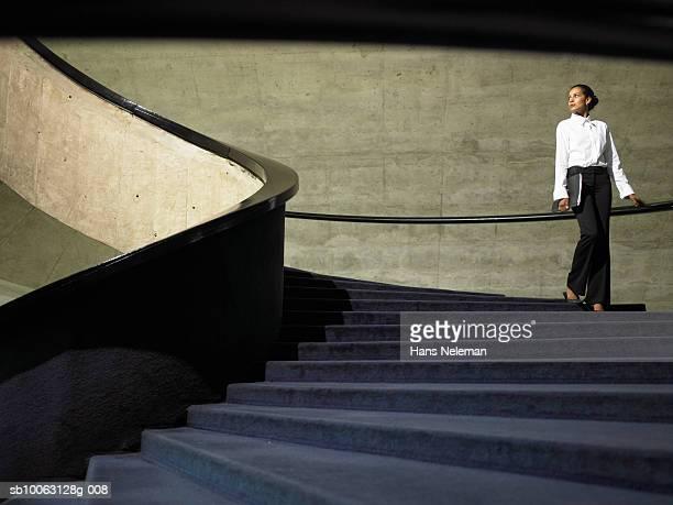 business woman walking down stairs in office, low angle view - bien vestido fotografías e imágenes de stock