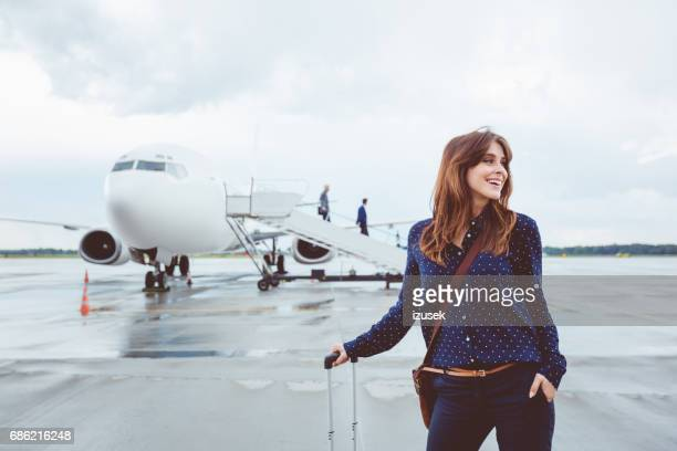 Business woman walking in front of airplane with luggage